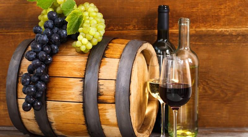 חבית יין ליד בקבוקים וכוסיות עם יין